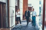 Full length of three people walking in hotel corridor - 249571649