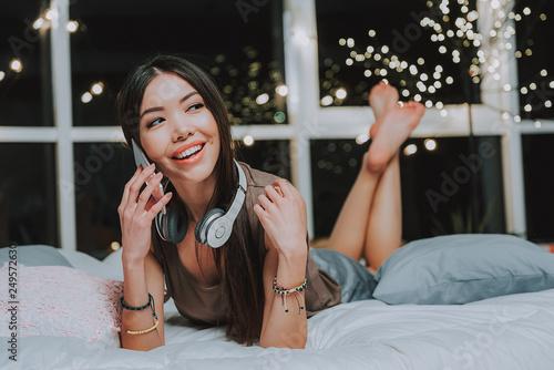 Leinwanddruck Bild Glad asian female telling at cellphone in her bed