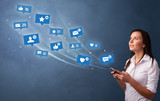 Young person using phone with flying social media icons around