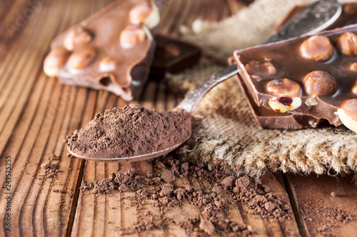 mata magnetyczna Pieces of chocolate bar with nuts, cocoa powder and sack napkin on the table.