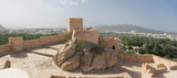 Walls and turrets of the Fort of Nahkal and the village with the mosque in the background (Oman) - 249585046