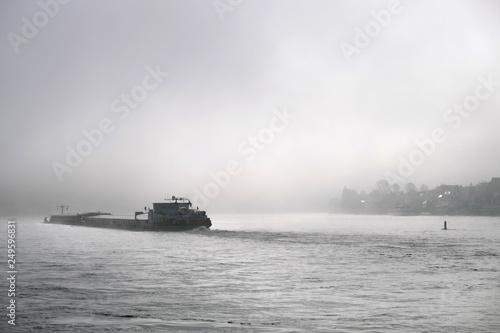 Frachtschiff auf dem Rhein im Nebel - Stockfoto