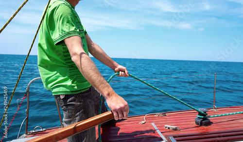 Man driving sailing yacht.