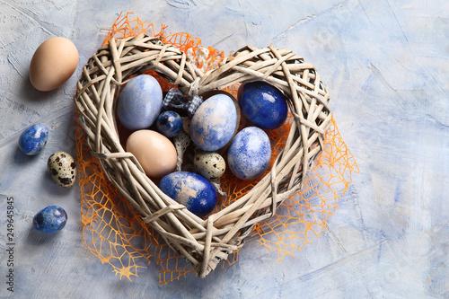 Leinwanddruck Bild Easter eggs in heart shaped nest