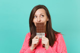 Pensive young woman in knitted pink sweater looking up, hold in hand, covering mouth with chocolate bar isolated on blue wall background, studio portrait. People lifestyle concept. Mock up copy space. - 249649481
