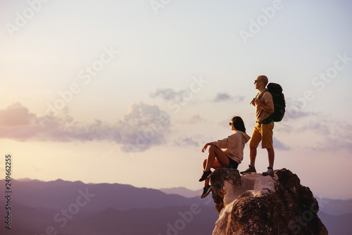 Couple of backpackers relaxing on big rock at sunset time. Space for text - 249662255