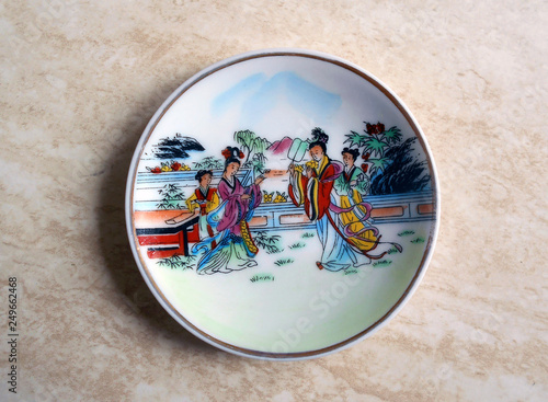 The Chinese antiquarian porcelain plate is made in national style. Women in vintage clothes are drawn on a plate. © galliina