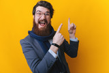 Handsome young businessman, waring a scarf and glasses, happy smile point finger to empty copy space, businessman showing pointing side, - 249664658