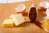 cocoa powder and blocks of butter, cake ingredients on baking paper - 249670673
