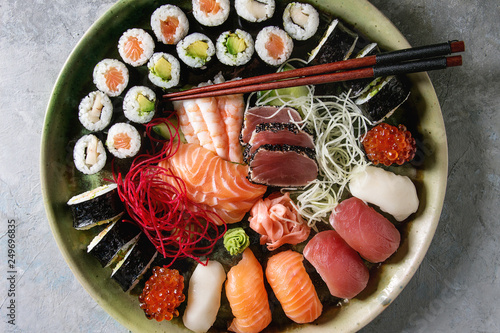 Sushi Set nigiri sashimi and sushi rolls in ceramic serving plate with salad and chopsticks over grey concrete background. Flat lay, space. Japan menu