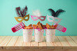 Jewish holiday Purim background with paper cup, carnival mask, noisemaker and hamantaschen cookies on wooden table.