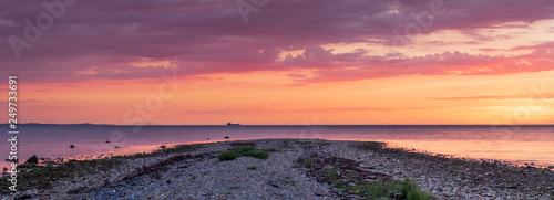 Panorama sunset over a stone beach with a dramatic colors and clouds. Hittarps revet is an unknown beauty in Helsingborg, Sweden.  - 249733691