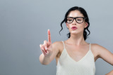 Young woman pointing at something on a solid background - 249750475