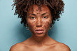 Leinwanddruck Bild - Skin care and cosmetology concept. Beautiful dark skinned serious female model has brown coffee scrub, does peeling of skin, wants to remove wrinkles, poses half nude over blue studio background