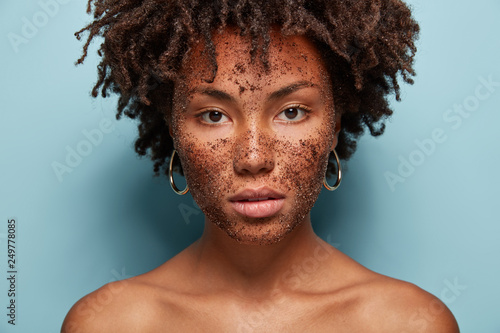 Leinwanddruck Bild Skin care and cosmetology concept. Beautiful dark skinned serious female model has brown coffee scrub, does peeling of skin, wants to remove wrinkles, poses half nude over blue studio background