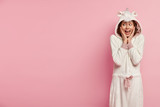 Image of positive woman touches cheeks, enjoys good morning, smiles positively, looks away on free space, dressed in soft domestic kigurumi costume, isolated on pink background. Sleeping concept - 249778497