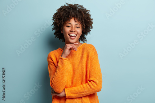 Optimistic Afro American woman with dark skin, curly hair, keeps hands partly crossed, looks at camera with pleasure, wears orange sweater, isolated over blue background. Happy emotions concept.