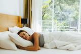 Woman sleeping on bed in hotel room - 249790827