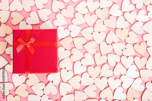 Wood hearts on pink background have a gift box, © sorapop