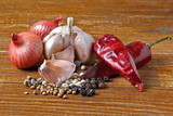 garlic, dry chili peppers, onion, green black and white peppercorns and coriander on wooden background - 249797868