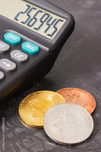Bitcoins with calculator, symbol of virtual money and cryptocurrency - 249803222