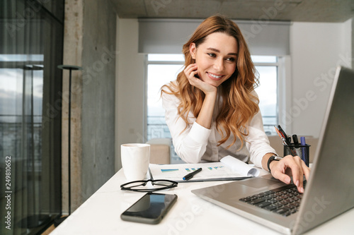 Business woman dressed in formal clothes shirt indoors using laptop computer.