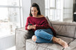 Leinwanddruck Bild - Beautiful woman indoors in home on sofa using mobile phone.