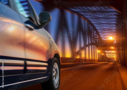 car driving at high speed at night through a truss bridge
