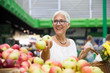 Senior woman buying apples on market