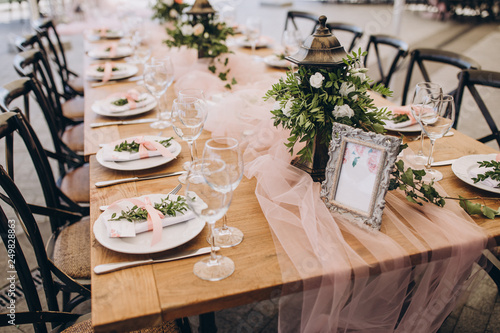 plates and glasses stand on the festive table, the table is decorated with flower compositions and cloth © alexgukalov