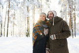 Waist up portrait of happy couple embracing in winter forest looking away dreamily, copy space - 249848458