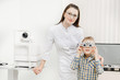 Leinwanddruck Bild - Pediatric Doctor ophthalmologist checks vision of child boy. Concept selection of glasses lenses.
