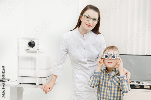 Leinwanddruck Bild Pediatric Doctor ophthalmologist checks vision of child boy. Concept selection of glasses lenses.