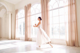 Young ballerina dancing in a white studio