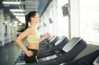 Young fit brunette female in activewear training on one of treadmills in sports center in front of window