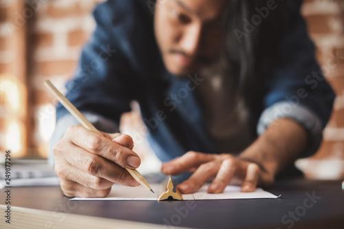 Leinwanddruck Bild Young Asian man draft a drawing plan for artwork, architect, engineering drawing, creative designer concept