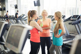 Friendly mature women in activewear dicussing something while enjoying break between trainings in fitness center