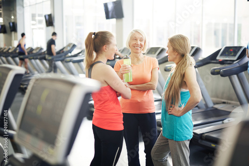 Friendly mature women in activewear dicussing something while enjoying break between trainings in fitness center - 249877414