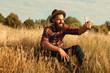 Bearded traveler taking selfie in field