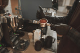 Man barista in an apron is holding a portafilter with coffee and ready for preparing espresso at the coffee shop. Close up photo of bartender with a holder with grinded coffee. - 249884024