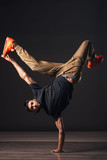 A man hip hop dancer or bboy freezes in one pose on the hand
