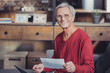 Positive pensioner feeling satisfied with his bills and smiling