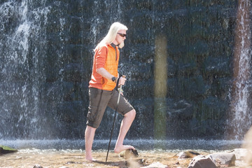 Young man posing for a camera in front of a waterfall