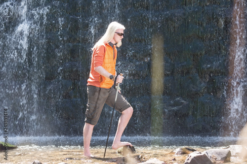Young man posing for a camera in front of a waterfall - 249891474