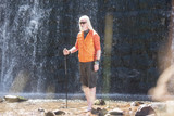 Young man with beard posing for a camera in front of a waterfall