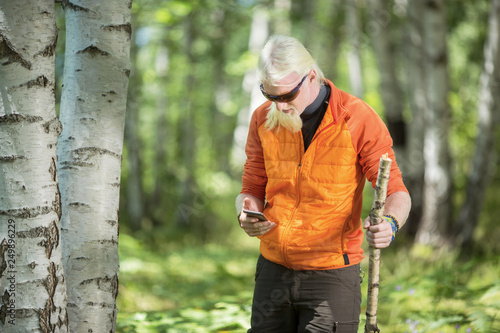 Young man with beard standing in nature in looking in to a smartphone