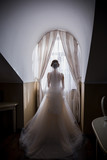 bride stands near the window