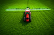 Tractor plowing and spraying on green agricultural field, aerial drone top view