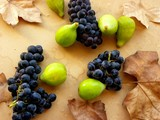bunch of grapes and figs on a wooden table