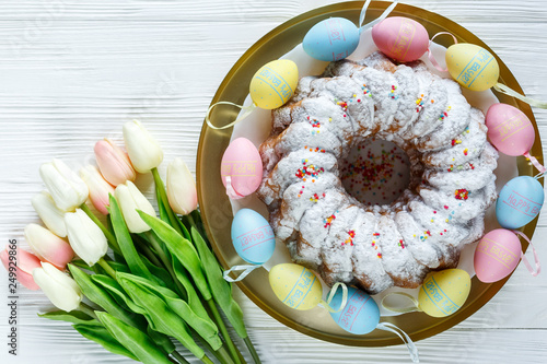 Happy Easter! Golden tray with plate wit cake and hand painted colorful eggs, tulips on white wooden table. Close up. Decoration for Easter, festive background. © Natali